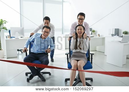 Asian business people racing on office chairs