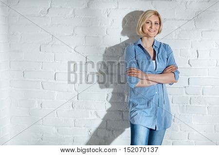 Confident young woman standing arms crossed front of white brick wall, smiling, looking at camera.