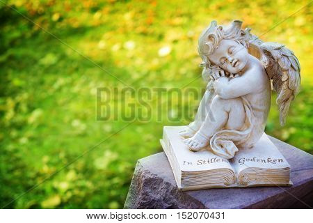 Grave Angel with book on grave stone
