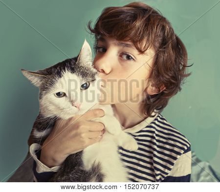 cat preteen handsome boy with tom cat kissing close up photo