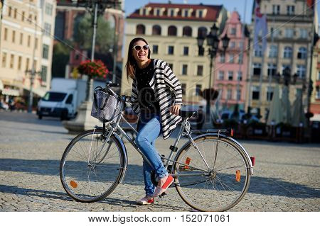 Cute young brunette in sunglasses with bicycle on a paved pavement. Sunny warm day. Beautiful buildings of the ancient European city cozy cafes flowers. Girl in a good mood she smiles.