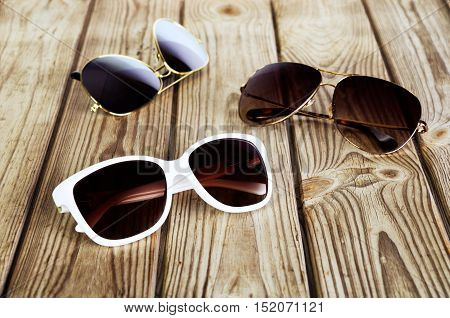 One White Woman's Sunglasses And Two Unisex Sunglasses Close-up On A Wooden Background