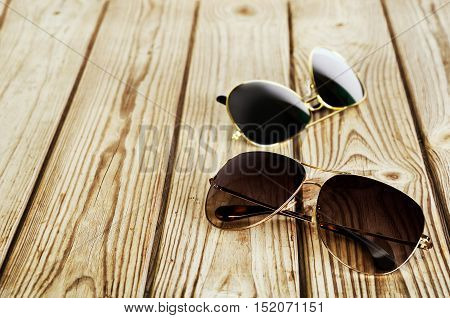 Two Unisex Sunglasses Close-up On A Wooden Background