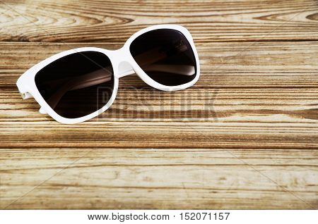 White Woman's Sunglasses Close-up On A Wooden Background