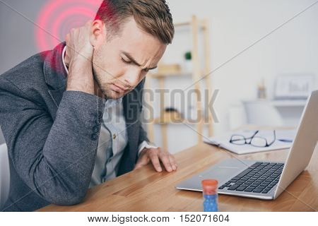 Need some rest. Handsome stressed young man feeling pain in his neck and using laptop while sitting by the table.