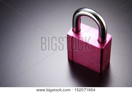pink color solid pad lock on the black background