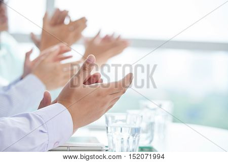 Close-up image of clapping business executives at meeting