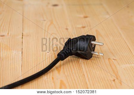 Hand holding a black electric plug on wood