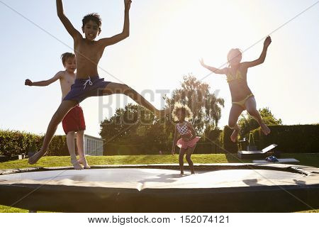 Group Of Children Having Fun Jumping On Outdoor Trampoline