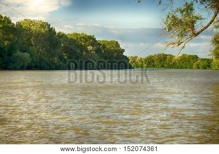Summer landscape. Tisza (Tisa) river at Tiszalok, Hungary. Sunny day. Summer season landscape. Cloudy blue sky. Gree forest. Cloudy blue sky.