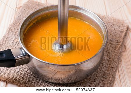 Pumpkin pureed for soup with blender  on wooden table