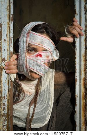 Woman in rags wearing bloody bandages standing in a rusty old window