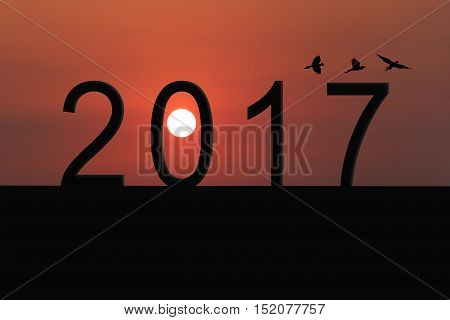 Silhouette of number 2017 on the house roof and sunset in twilight skyconcept of the New Year and Christmas.