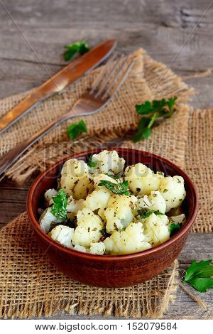 Marinated cauliflower with spices and parsley. Marinated cauliflower in an earthenware bowl and on an old wooden table. Rustic style. Closeup