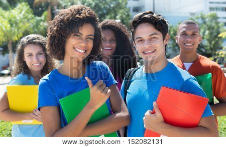 Group of five laughing latin american caucasian and african students outdoor in the city in summer
