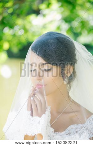 sexy bride woman with pretty face under wedding veil on sunny summer day outdoor on blurred background