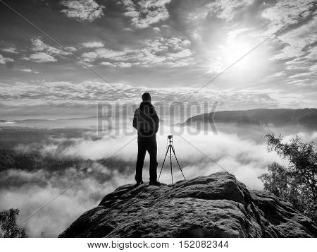 Professional Photographer With Tripod On Cliff And Thinking. Dreamy Fog
