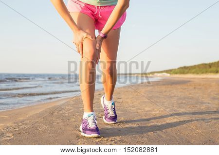 Woman holding her hurting knee while working out