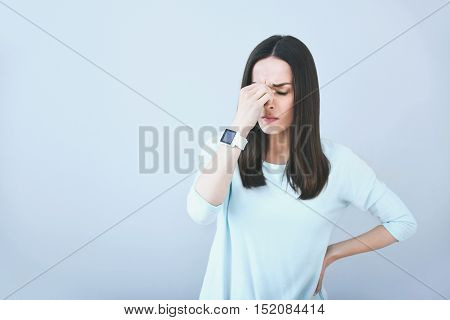 Hard to relax. Good looking unhappy woman feelling tired and closing her eyes while standing against white isolated background.
