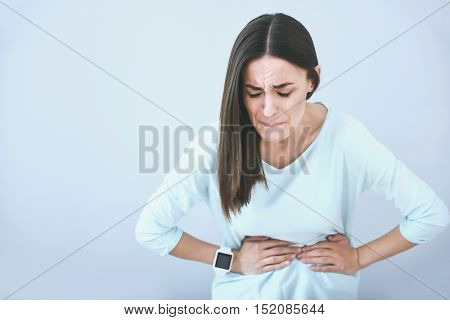 Sudden pain. Brown haired young woman biting her lip and putting arms on her belly while standing against white i background.