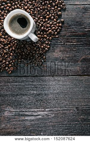 White ceramic cup of coffee on the table covered with coffee beans. Flat lay