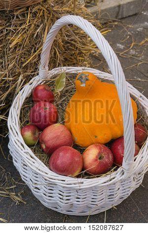 white wicker basket with red apples and orange pumpkin near haystack