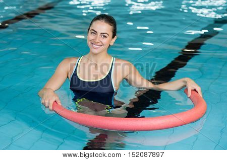 Happy smiling woman doing exercise with aqua tube in a swimming pool. Young sportive woman exercising in swimming pool with the help of a tube. Young heallthy woman doing aerobics in swimming pool.