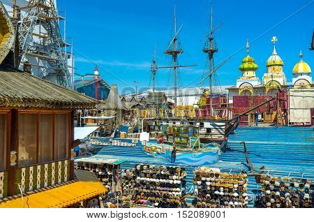 MOSCOW RUSSIA - MAY 10 2015: The wooden ship sails in painted timbered sea in the middle of the souvenir Vernissage market in Izmailovo on May 10 in Moscow.