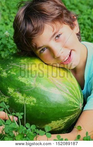 preteen boy smiling hug whole water melon lay on green summer grass