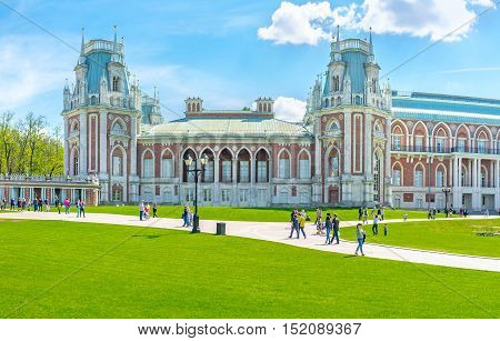 MOSCOW RUSSIA - MAY 10 2015: The facade of the Grand Palace of Tsaritsyno Royal Residence decorated with towers patterns fretwork and surrounded by lawn on May 10 in Moscow.