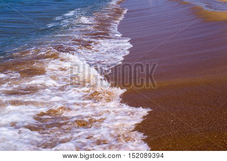 sea surf and wave with white foam on the sandy coast closeup
