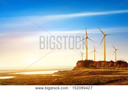 Silhouette of wind power station on sunset