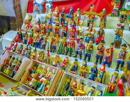 The handmade Christmas toys in vintage costumes in the stall of Izmailovsky market Moscow Russia.