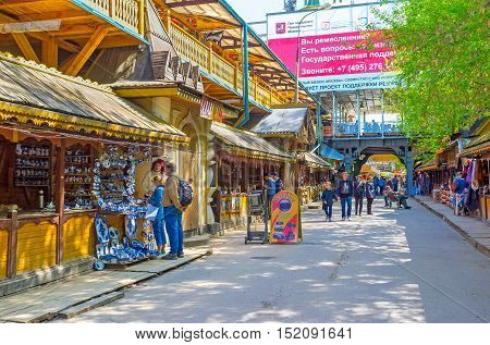 MOSCOW RUSSIA - MAY 10 2015: The tourists choose the souvenirs of Gzhel porcelain famous russian style ceramics on May 10 in Moscow.