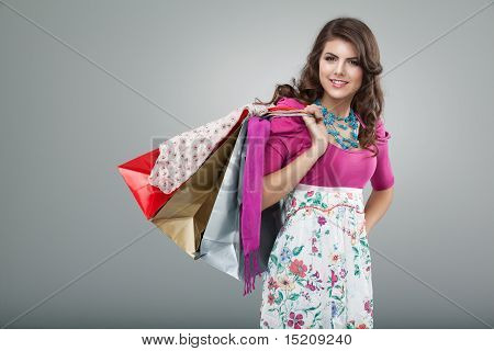 Young Woman In Colourful Outfit Holding A Few Shopping Bags, Smiling