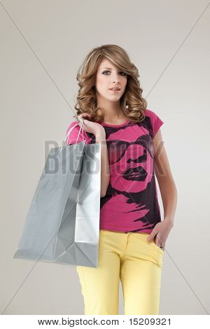 Young Blonde Woman In Colourful Outfit Holding A Shopping Bag, Smiling