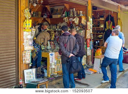MOSCOW RUSSIA - MAY 10 2015: The tourists at the numismatic shop of Izmailovsky market choose old coins stamps military awards retro postcards on May 10 in Moscow.