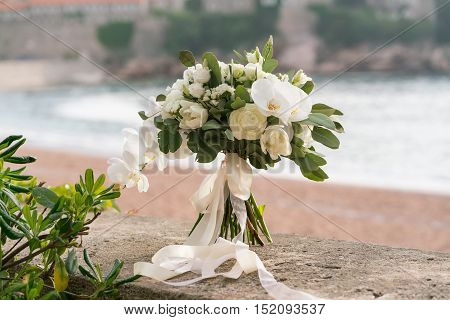 bridal bouquet of orchids, ranunculuses, tulips and eucalyptus, white and green