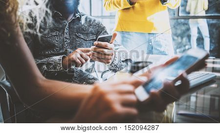 Closeup of young coworkers using electronic gadgets in sunny office.Man holding a smartphone his hands and woman touching screen her mobile phone. Horizontal, blurred