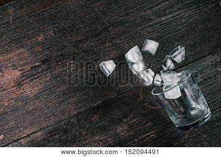 Whiskey glass with ice cubes lying on the dark wood surface. Flat lay