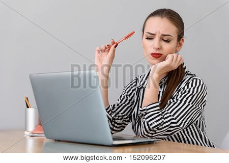 Focused on hard task. Bored young businesswoman staring at her laptop screen isolated on grey background