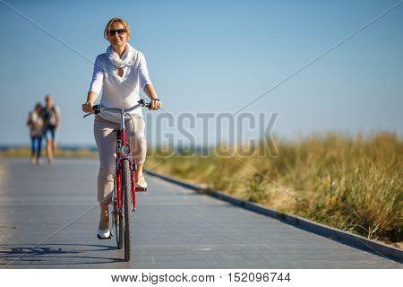 Woman riding bike at seaside
