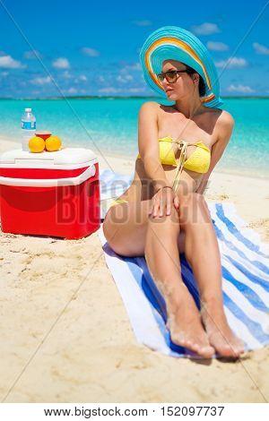 Woman in bikini sunbathing on the beach in Exuma, Bahamas