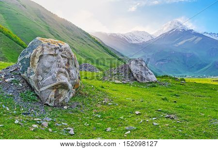 The stone faces of famous Georgian writers and poets on the green meadow of Sno village Kazbegi Georgia.