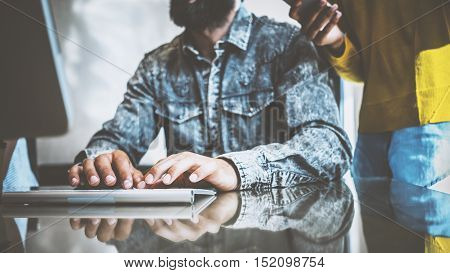Young coworkers discussing business ideas at workplace.Man using desktop computer.Woman standing close him and holding smartphone in her hand. Horizontal, blurred