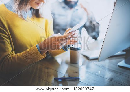 Working process in modern office.Smiling woman looking to her mobile phone and typing message at the wooden table.Horizontal photo, blurred background