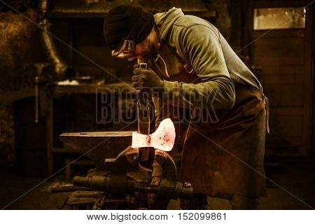 Blacksmith forging the molten metal on the rusty vise in smithy