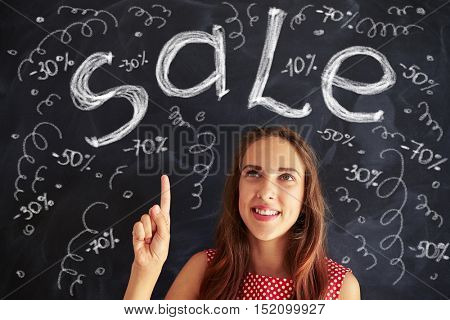 Pretty teenage girl is pointing up at the chalk drawings on blackboard notifying of sale and discount
