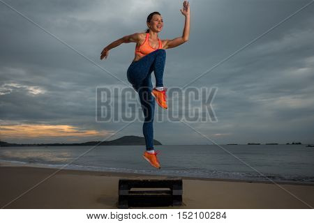 fitness, training, aerobics and people concept - girl working out with steppers on the beach