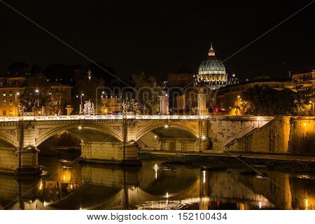 Night view at St. Peter's cathedral and bridge over Tiber river in Rome, Italy